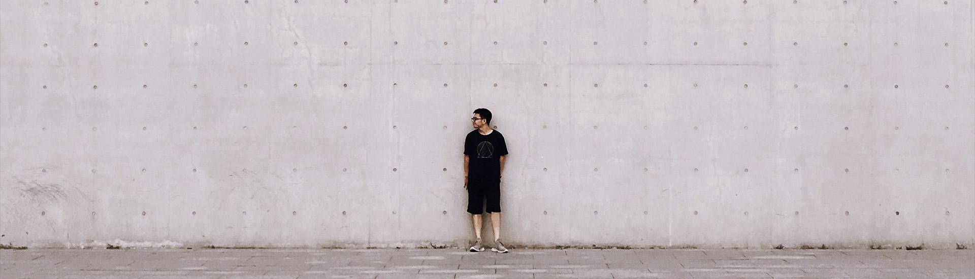 Junger Mann vor Mauer